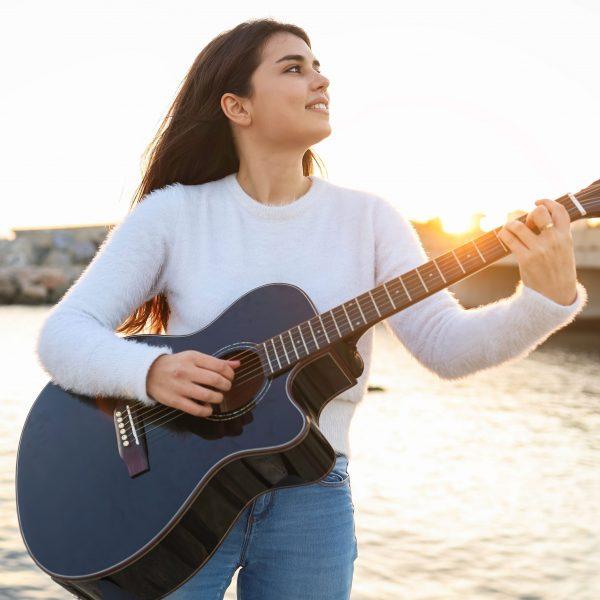 Jugendliche Gitarristin spielt akustische Gitarre