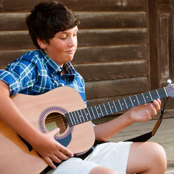 Jugendlicher Anfänger mit akustischer Gitarre